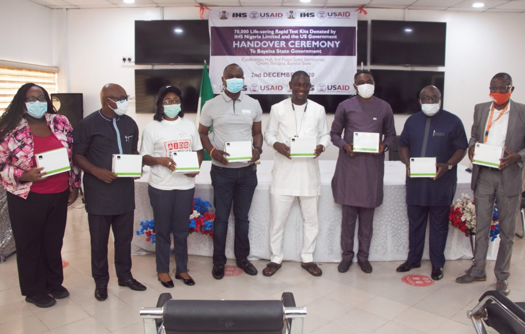 Photo caption: Bayelsa State Commissioner for Health Dr. Pabara Newton Igwele (center, in white), receives 70,000 HIV test kits from IHS Nigeria with support from USAID under a private-public partnership with the telecoms giant
