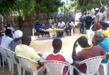Mrs Yelwa sitting in the Middle of two men as one of the Executive of VSLA Pro-Act project in Dumne Community of Adamawa State